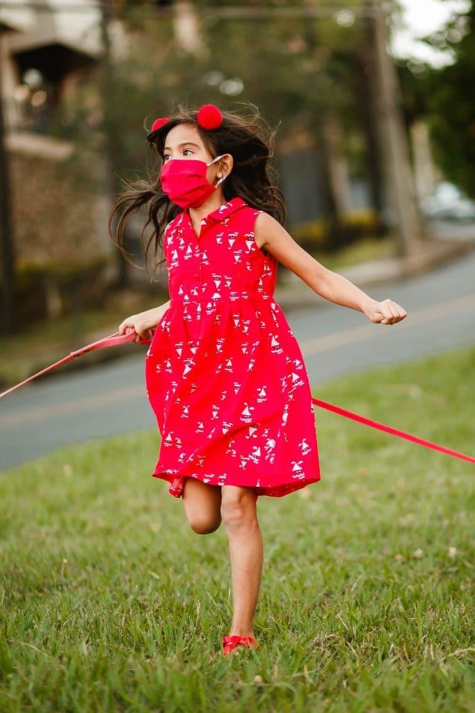 petite fille qui joue dehors avec un masque